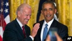 Wapres AS Joe Biden, kiri, dan Presiden Barack Obama bereaksi setelah memerintahkan seorang aktivis berulangkali mengganggu pidatonya keluar dari Ruangan Timur Gedung Putih pada sebuah resepsi merayakan Bulan LGBT di Washington, Rabu (24/6).