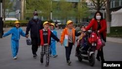 北京一所小學校的家長在接放學的孩子回家。 (2021年4月6日)