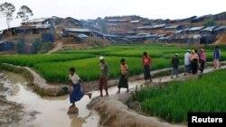 Refugiados rohingya cruzan un canal acuático en el improvisado campo de refugiados en Bangladesh, el 13 de septiembre, de 2013.