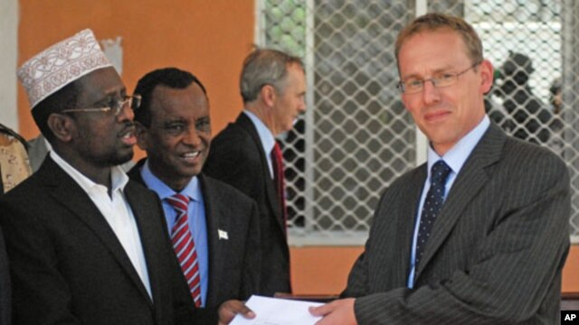 Somali President Sheik Sharif Sheik Ahmed (L) receives diplomatic credentials from the Britain's new ambassador to Somalia  Matt Baugh (R) at the Hilltop presidential palace in Mogadishu, Somalia, February 2, 2012.