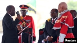 FILE - Tanzania's President-elect John Magufuli (L) takes the Oath of Office during his inauguration ceremony at the Uhuru Stadium in Dar es Salaam, Nov. 5, 2015.