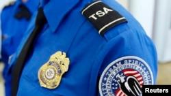 Značka, amblem i inicijali Uprave za bezebdnost saobraćaja na jednom od zaposlenih na aerodromu u Los Anđelesu