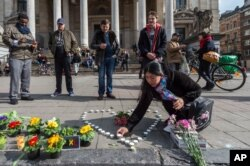A woman places candles in the shape of a heart outside the stock exchange in Brussels, March 22, 2016.