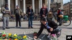 Une femme installe des bougies en forme de cœur à Bruxelles, le mardi 22 mars 2016.