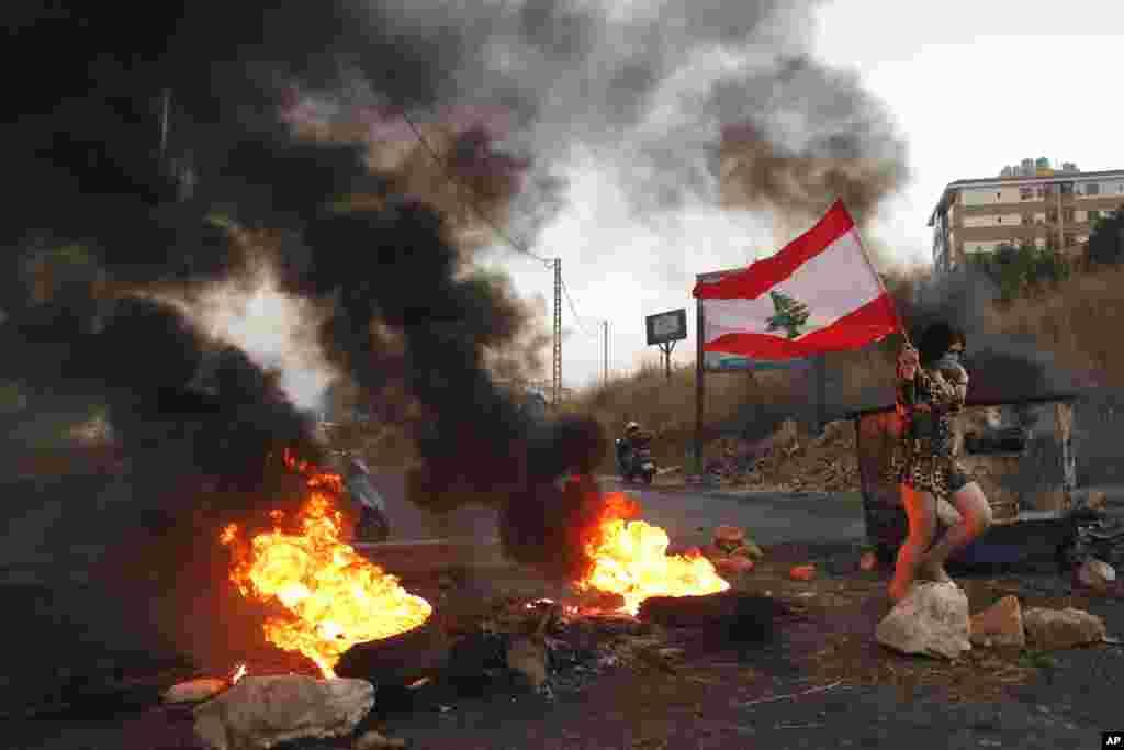 یک زن معترض پرچم لبنان را در جنوب بیروت پایتخت این کشور در دست دارد. معترضان به مشکلات اقتصادی و بیکاری اعتراض دارند.