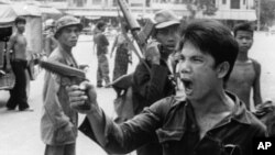 A Khmer Rouge soldier waves his pistol and orders store owners to abandon their shops in Phnom Penh, Cambodia on April 17, 1975 as the capital fell to the communist forces. A large portion of the city's population was reportedly forced to evacuate.