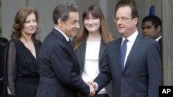 El saliente presidente, Nicolas Sarkozy, y el entrante mandatario, François Hollande, escoltados por la compañera de Hollande, Valerie Trerweiler, y Carla Bruni-Sarkozy durante la ceremonia de traspaso del mando.