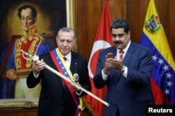 FILE - Turkish President Recep Tayyip Erdogan holds a replica of the sword of national hero Simon Bolivar, next to Venezuela's President Nicolas Maduro, during an agreement-signing ceremony between Turkey and Venezuela at Miraflores Palace in Caracas, Venezuela,