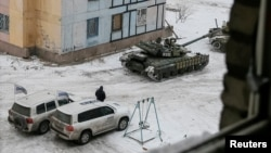FILE - Organization for Security and Cooperation in Europe (OSCE) vehicles are seen behind tanks in the government-held industrial town of Avdiivka, eastern Ukraine, Feb. 1, 2017.