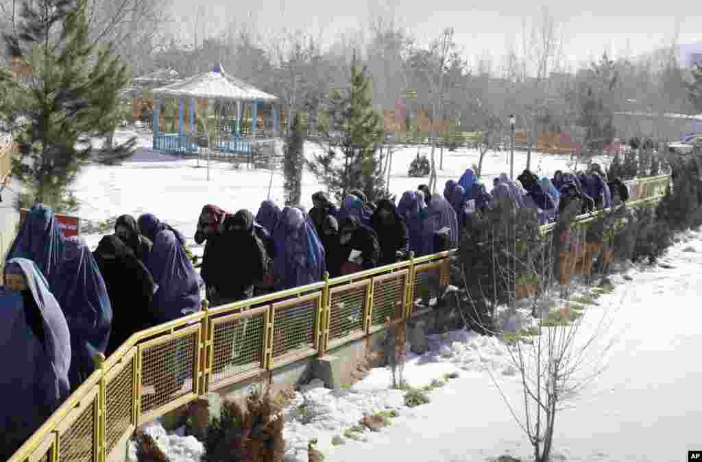Afghan women walk to receive food and other winter assistance donated by the UNHCR in Kabul, Afghanistan, January 2, 2013.