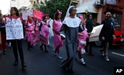 A young woman dressed as a nun leads a group of women depicting pregnant schoolgirls in a march marking the International Day for the Elimination of Violence Against Women, in Asuncion, Paraguay, Nov. 25, 2017. According to officials there is at least one femicide reported per week in Paraguay.
