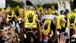 Protesters hold placards with the symbol of Rabaah al-Adawiya mosque, where supporters of Egypt's ousted President Morsi held a sit-in that was violently dispersed, Cairo, Sept. 13, 2013.