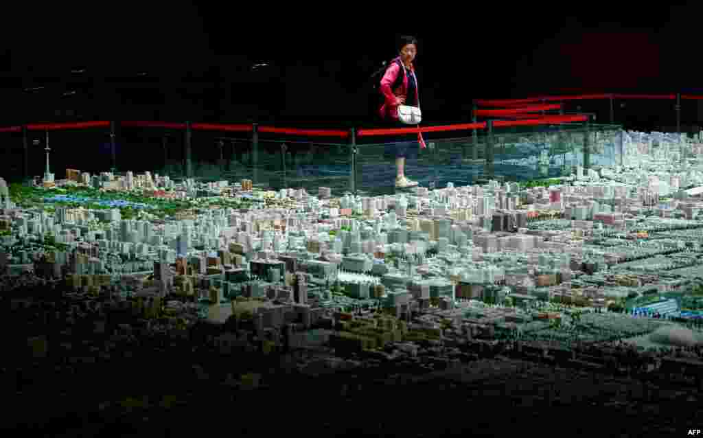 A woman looks at a scale model of Beijing's urban development at an exhibition center in Beijing, China.