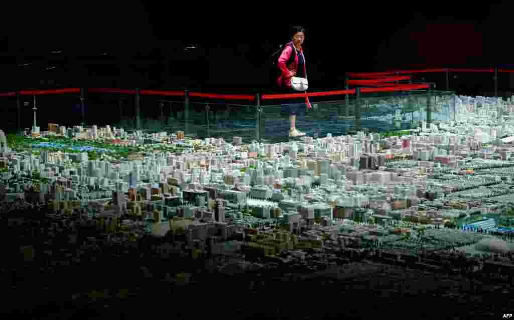 Một người phụ nữ ngắm nhìn mô hình thu nhỏ dự án quy hoạch phát triển đô thị Bắc Kinh tại một trung tâm triển lãm ở Bắc Kinh, Trung Quốc.