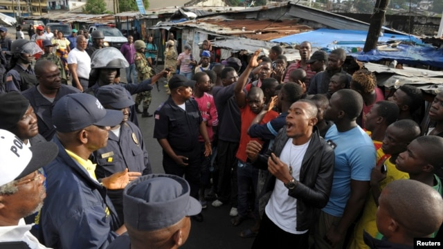 Members of Liberian security forces talk with a protester in the West Point neighbourhood in Monrovia Aug. 20, 2014.