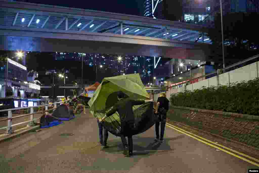Pro-democracy protesters move a tent along a road outside the government headquarters at Admiralty in Hong Kong, Dec. 8, 2014.