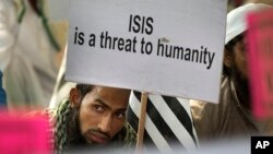 FILE - An Indian Muslim man holds a banner during a protest against IS, an Islamic State group, and the Paris attacks, in New Delhi, India, Nov. 18, 2015.