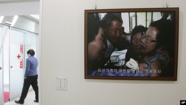 A picture of the reunion of family members from North and South Korea in 2010 is displayed at the headquarters of the Korea Red Cross in Seoul, South Korea, Jan. 7, 2014.
