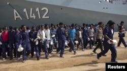 Des migrants marchent sur le quai après avoir débarqué du navire de la marine allemande Frankfurt Am Main dans le port sicilien d'Augusta, Italie, le 12 Avril 2016.