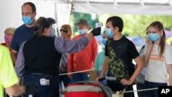 13 Haziran 2020 - Missouri'de bir mağaza çalışanları Corona virüsüne karşı önlem olarak müşterilerin ateşini ölçüyor