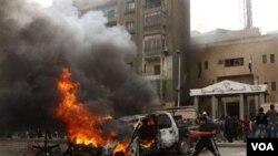 Demonstran Mesir membakar sebuah mobil di depan kantor polisi dekat piramida di Giza.