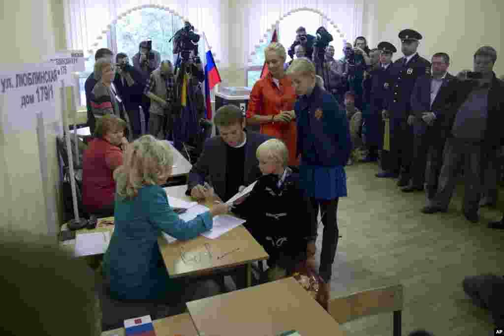 Ứng cử viên đối lập Alexei Navalny nhận phiếu bầu hôm 8/9 bên cạnh vợ và hai con.