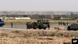 FILE - Iraqi soldiers patrol along the border between Syria and Iraq in Qaim, located in the Euphrates river valley 200 miles (320 kilometers) west of Baghdad, Iraq, July 20, 2012.