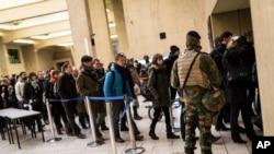 Binh sĩ Bỉ canh gác trong lúc hành khách xếp hàng để kiểm tra túi xách tại các nhà ga ở trung tâm Brussels, ngày 23/3/2016.