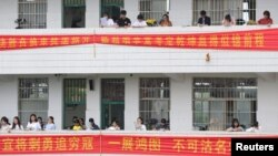 Students study along corridors at a high school ahead of the annual national college entrance examination, in Hengyang, Hunan province, China, June 3, 2018. In nearby Leiyang, parents protested a plan to move students from overcrowded schools. Parents were concerned about formaldehyde in the dormitory.