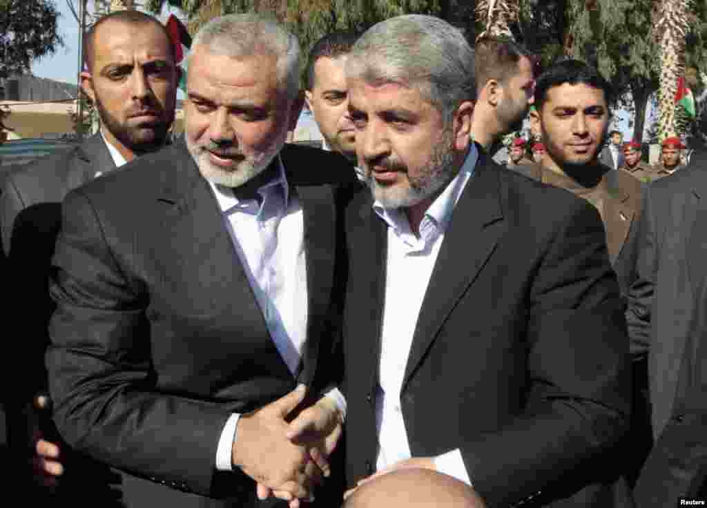 Hamas chief Khaled Meshaal (front R) walks with senior Hamas leader Ismail Haniyeh (front L) upon his arrival at the Rafah crossing in the southern Gaza Strip, December 7, 2012.