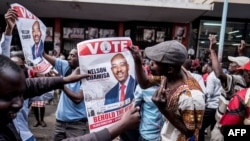 Supporters of Zimbabwean opposition MDC Alliance party leader Nelson Chamisa hold his campaign posters as they gather outside the MDC Alliance's headquarters in Harare on July 31, 2018.