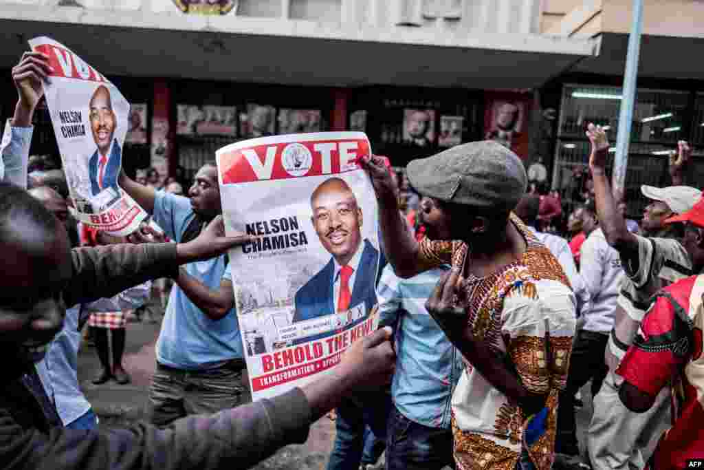 Supporters of Zimbabwean opposition MDC Alliance party leader Nelson Chamisa hold his campaign posters as they gather outside the MDC Alliance's headquarters in Harare. The government warned election candidates they faced prosecution and jail for prematurely announcing results of landmark polls after the main opposition MDC party said it had won.
