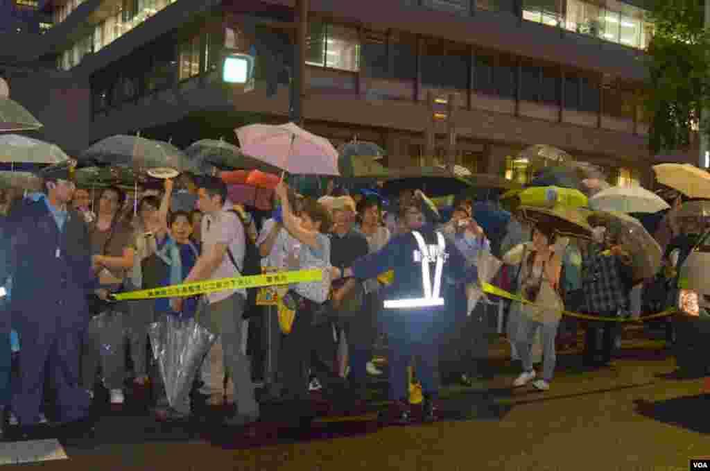 Демонстранти за огорожею встановленою поліцією.