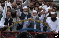 FILE - The leader of Hizbul Mujahideen, Syed Salahuddin, second left front, and the head of Jamaat-e-Islami, a Pakistani religious party, Sirajul Haq, third left front, and others lead an anti-Indian rally in Lahore, Pakistan, July 31, 2016.
