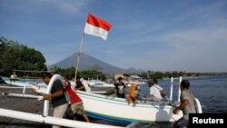 Nelayan Indonesia bersiap berlayar ke laut, dengan latar belakang Gunung Agung, di Bali. (Foto: dok). Lima nelayan tradisional asal Kabupaten Langkat, Sumatera Utara (Sumut), dikabarkan ditangkap oleh polisi maritim Malaysia, Selasa (25/9).