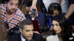 29일 이집트 카이로 법원에서 알자지라 방송사 기자인 캐나다인 아말 모하마드 파흐미(왼쪽)와 이집트인 바헤르 모하미(왼쪽 위)가 선고에 앞서 기자들의 질문에 답하고 있다. 오른쪽은 파흐미의 변호사인 아말 클루니.