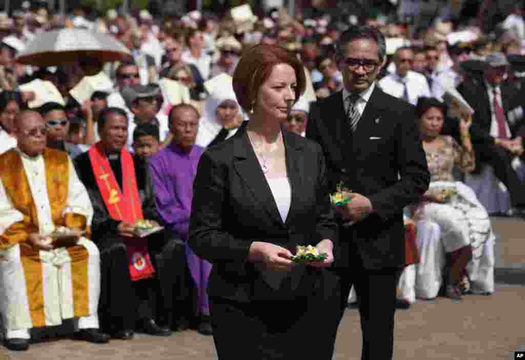 ນາຍົກລັດຖະມົນຕີອອສເຕຣເລຍ ທ່ານນາງ Julia Gillard, ຊ້າຍ, ຍ່າງໄປກັບລັດຖະມົນຕີການຕ່າງປະເທດ ອິນໂດເນເຊຍ ທ່ານ Marty Natalegawa ເພື່ອເອົາດອກໄມ້ໄປວາງ ໃນລະຫວ່າງພິທີຄົບຮອບ 10 ປີ ຂອງການໂຈມຕີທີ່ເກາະ Bali, ວັນທີ 12 ຕຸລາ 2012.