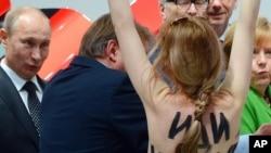 ຜູ້ປະທ້ວງທີ່ແກ້ເສື້ອຄົນນຶ່ງ ຍ່າງເຂົ້າໄປຫາ ປະທານາທິບໍດີຣັດເຊຍ ທ່ານ Vladimir Putin (ຜູ້ຈ້ອງເບິ່ງ) ແລະນາຍົກລັດຖະມົນຕີເຢຍລະມັນ ທ່ານນາງ Angela Merkel (ເສື້ອຂຽວ) ໃນພິທີເປີດງານວາງສະແດງ ສິນຄ້າອຸດສາຫະກໍາ ທີ່ເມືອງ Hannover, ເຢຍລະມັນ, ວັນທີ 8 ເມສາ 2013.