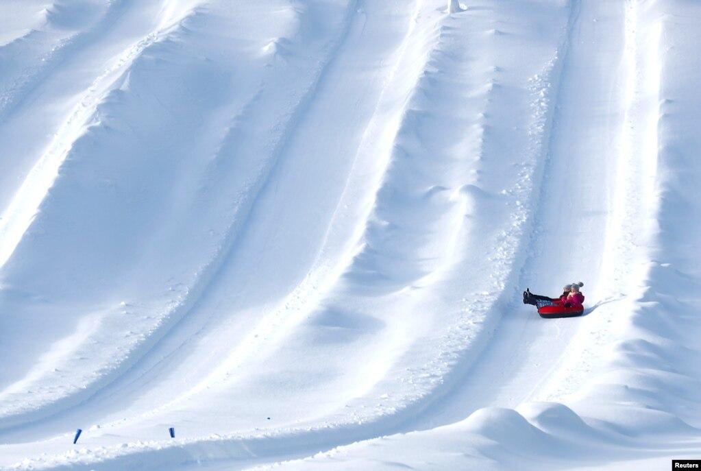 에스토니아 오테파(Otepaa)에서 어린 아이들이 눈이 쌓인 비탈길을튜브를 타고 내려오고 있다.