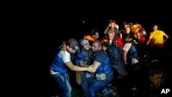 来自土耳其的难民抵达希腊东北部沿岸,两名叙利亚难民从小艇上把一位老年妇女抬上岸。