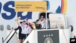Ðội trưởng Philip Lahm tay cầm cúp vàng vô địch World Cup và các đồng đội bước ra khỏi máy bay tại phi trường Tegel.