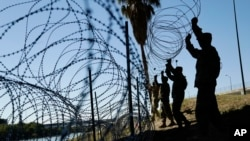 Members of the U.S. military install multiple tiers of concertina wire along the banks of the Rio Grande near the Juarez-Lincoln Bridge at the U.S.-Mexico border, Nov. 16, 2018, in Laredo, Texas.