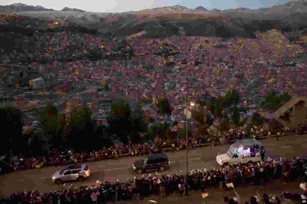 Pope Francis rides in his popemobile as he greets people lining the road from El Alto to La Paz, upon his arrival in Bolivia, July 8, 2015.