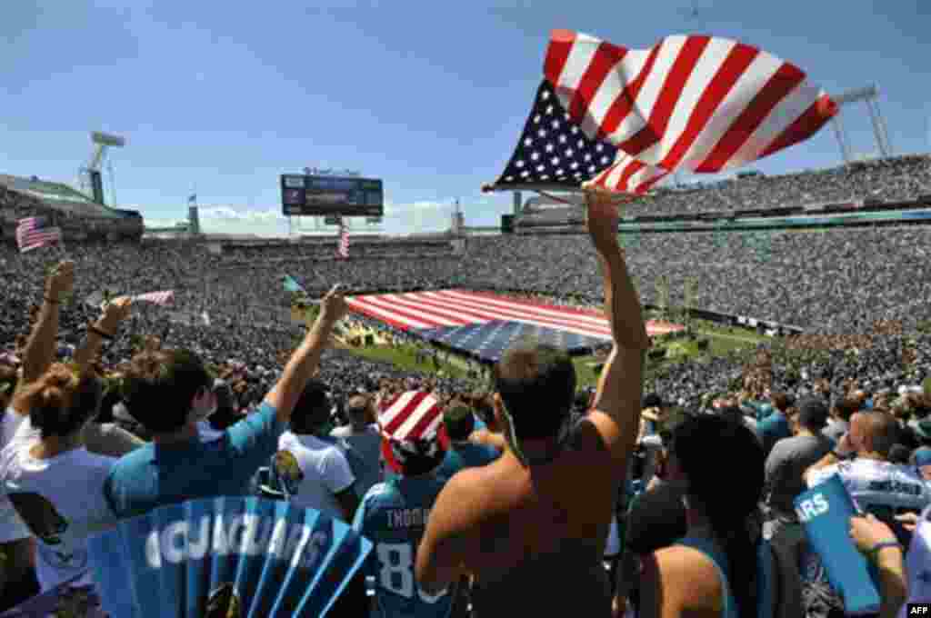 Fans cheer during a ceremony in commemoration of the 10th anniversary of the 9/11 terrorist attacks before an NFL football game between the Jacksonville Jaguars and the Tennessee Titans, Sunday, Sept. 11, 2011, in Jacksonville, Fla. (AP Photo/Stephen Mort