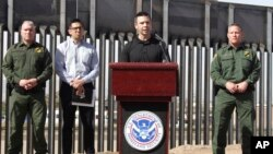 FILE - Customs and Border Protection Commissioner Kevin McAleenan, center, announced that the Trump administration will temporarily reassign several hundred border inspectors during a news conference at the border in El Paso, Texas, March 27, 2019.