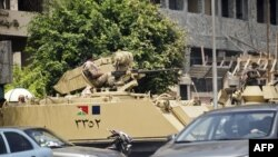 Egyptian army armoured personnel carriers (APC) are stationed outside the Aguza Military Hospital in Cairo, August 19, 2013.