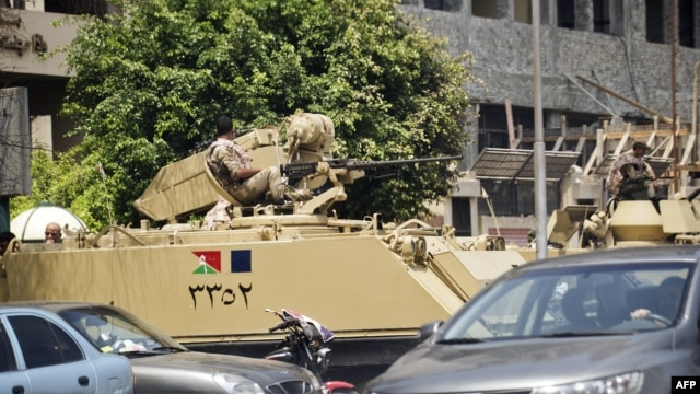 Egyptian army armored personnel carriers are stationed outside the Aguza Military Hospital in Cairo, August 19, 2013.