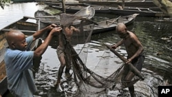 Fishermen sort out their fishing net at the bank of a polluted river in Bidere community in Ogoniland in Nigeria's delta region, August 20, 2011.