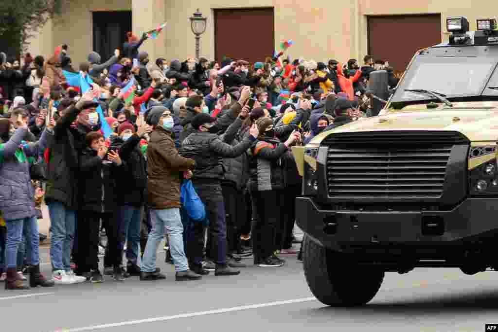 People greet Azerbaijani servicemen riding in military vehicles during a parade marking Azerbaijan's victory against Armenia in their conflict for control over the disputed Nagorno-Karabakh region, in Baku.