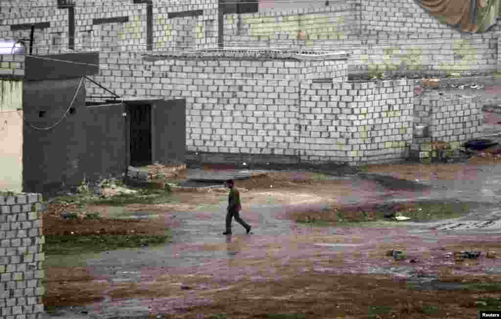 A Syrian man walks in front of his house during heavy rain in the northern Syrian town of Ras al-Ain, as seen from the Turkish border town of Ceylanpinar, Sanliurfa province, November 23, 2012.